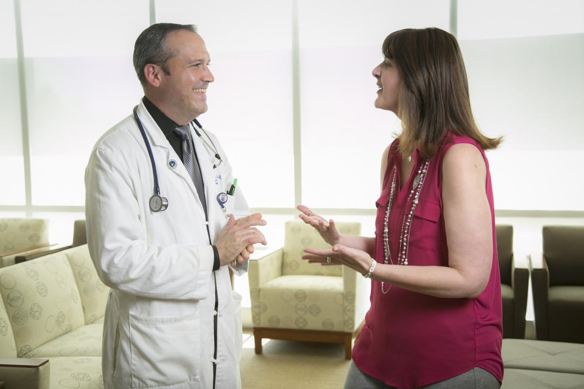 """Tricia Gallagher said she doesn't mind when her appointment is delayed because she knows that her oncologist Brent Hanks, MD, PhD, takes care to spend time with each individual patient. """"I can't even come up with the words to describe how much I respect and just adore Dr. Hanks,"""" she said. """"He was placed in my path."""" (photo by Jared Lazarus, Duke Photography, April 14, 2017)"""