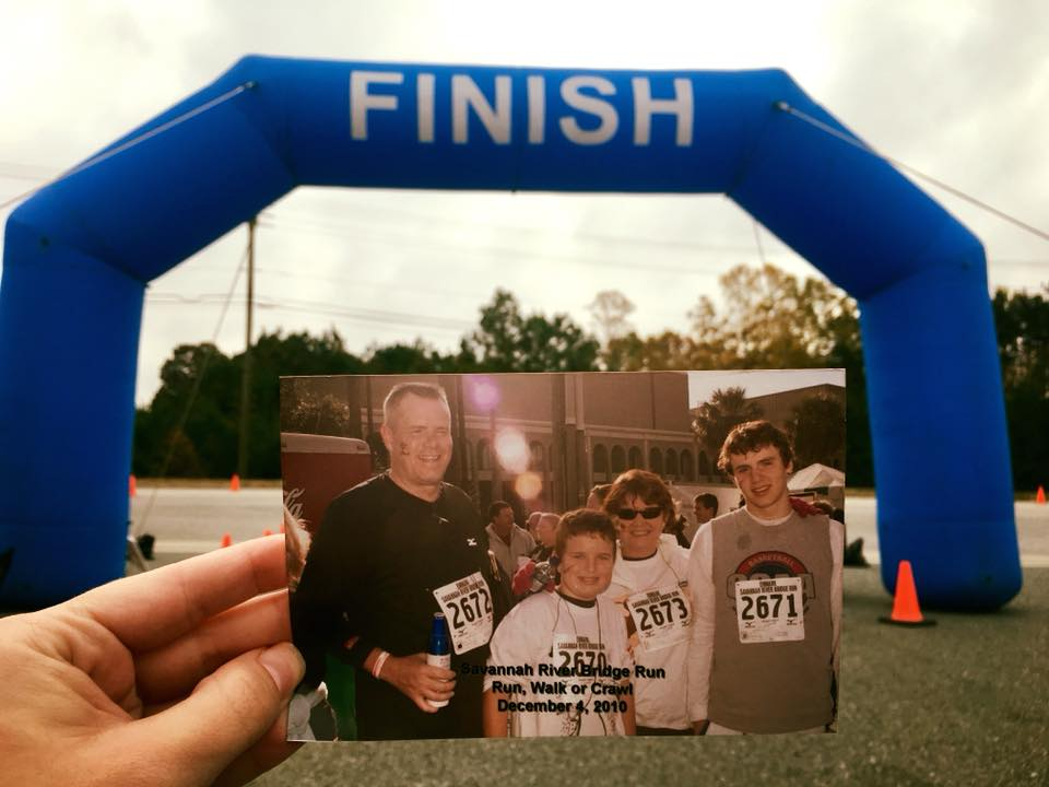A picture of the Symons family finishing a 5K in Savannah, GA, is being held at the finish line of the 5K they held in memory of their husband and father, Rick.
