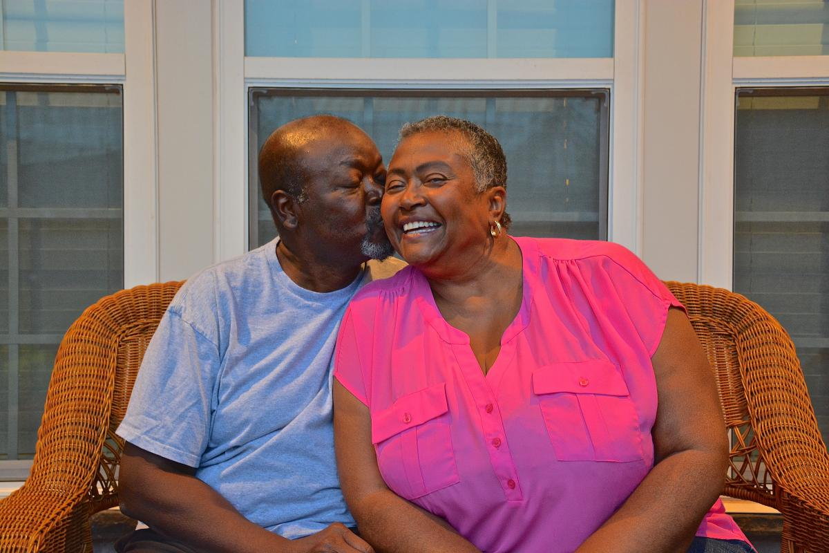 Ann gets a smooch from Ivin while sitting on the front porch. A former high school teacher, Ann is now enjoying her retirement years in the couple's new home in Durham, North Carolina.