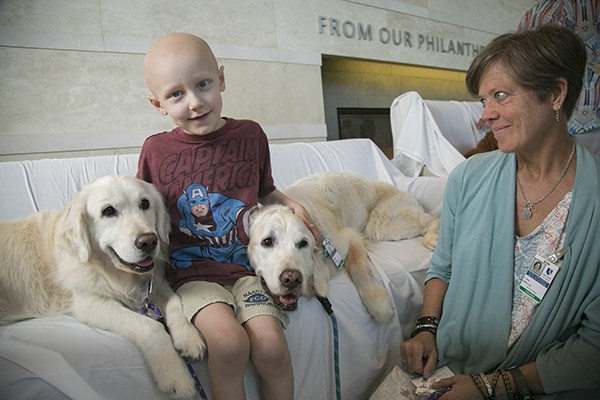 Ben Helton bonds with Pets At Duke golden retrievers while their therapy partner and Pets At Duke volunteer Lisa Well looks on.