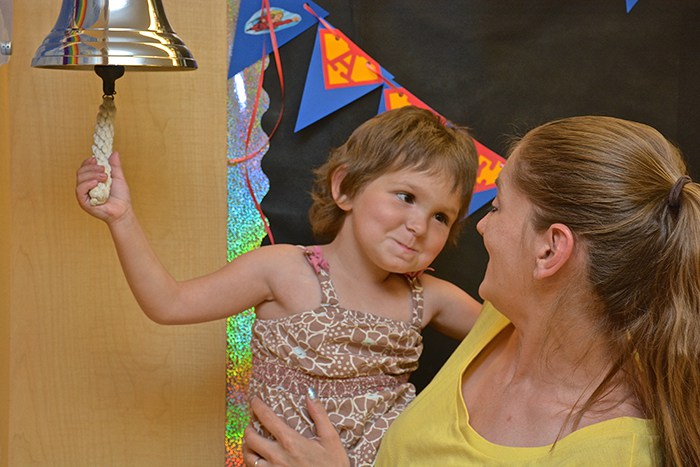Four-year-old Vanessa Burnette gives her mom, Laura, a sly smile as she rings the End of Treatment Bell. Vanessa, who was treated for stage 4 neuroblastoma at Duke Children's Health Center, was the first to ring the bell after its recent installation.