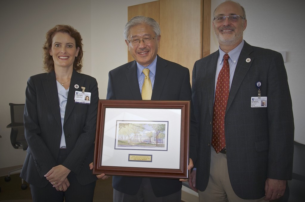 Chancellor Victor J. Dzau, M.D., president and CEO, Duke University Health System, accepts a farewell gift from DCI senior leadership, Carolyn Carpenter, MHA, FACHE, administrator & assoc. dean, and Michael B. Kastan, MD, PhD, executive director.