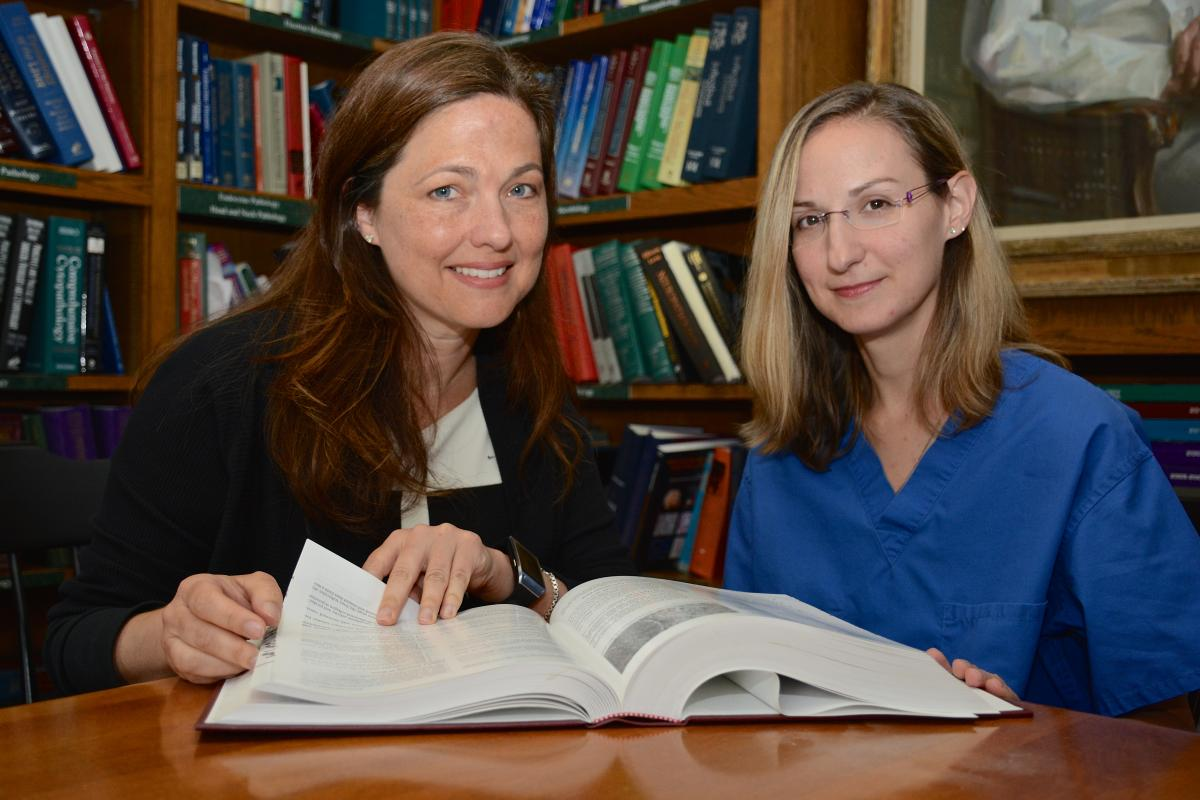 Shannon McCall, MD, director of the BRPC, and Alexis Sharp, senior laboratory administrator, consult in the Pathology Library of the Davison Building.