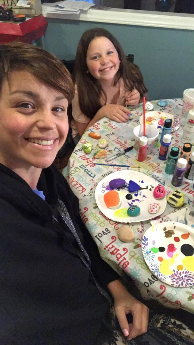 "Ashley Reaves Linden and her daughter Lilly painting ""rocks of hope."""
