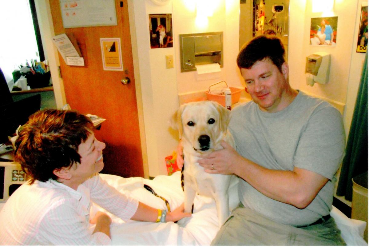 Bethany and her husband enjoying the company of a friend from pet therapy during a stay in the hospital for her HD IL-2 treatments.