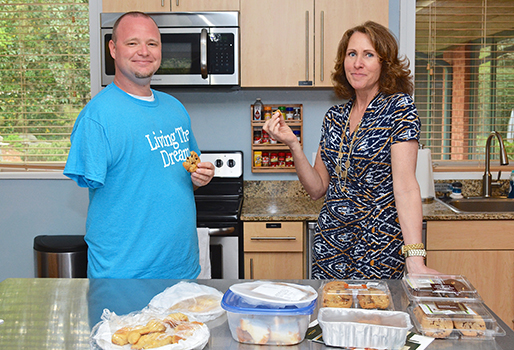 Hickory resident Brandon Lail, who in May 2014 lost his right arm to chondrosarcoma, enjoys a chocolate chip cookie with Kelly Mulhern, director of operations at Caring House.