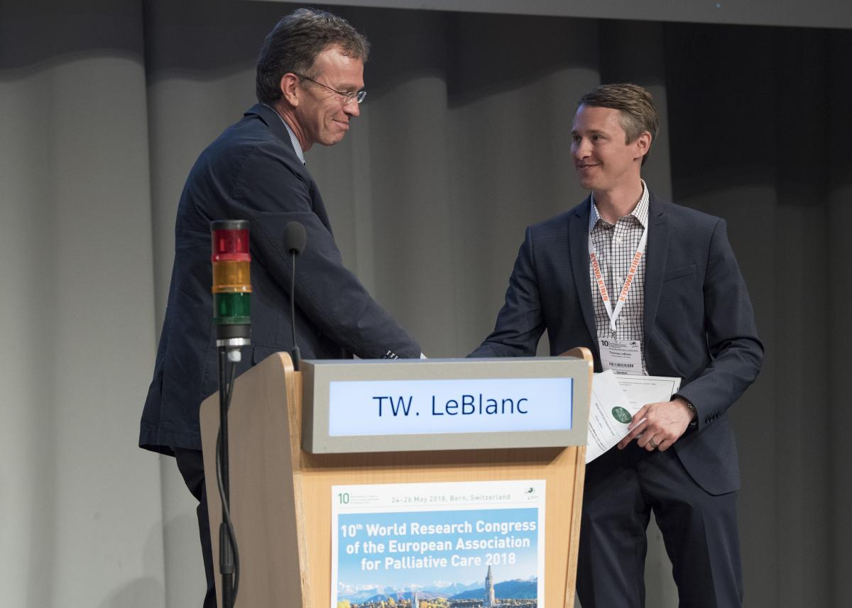 Thomas LeBlanc, MD, receives the 2018 EAPC Clinical Impact Award from Professor Steffen Eychmüller at the 10th EAPC World Research Congress in Bern, Switzerland, held this May. (photo by Lukas Lehmann, courtesy of EAPC)