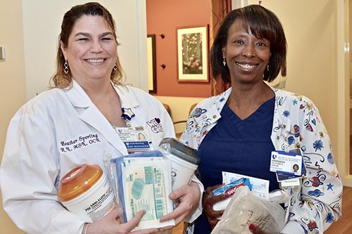Ebron poses with Holding supplies she will take with her on her upcoming mission trip, Heather Sperling, MSN, RN, OCN, nurse manager for the Women's  Cancer Clinic 2-2, 2-3 and Centralized Triage.