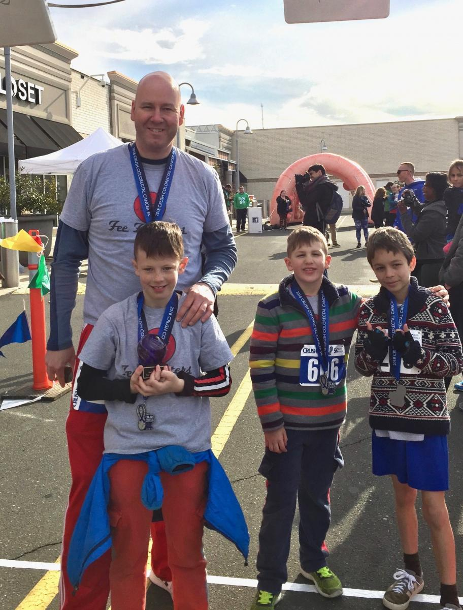 Frank Fee and his sons Callin and Ryan (left and middle) and their friend gather at the finish line for photos. Frank Fee is captain of the Fee Fighters!, formed last year in support of Fee's wife Mary Beth.