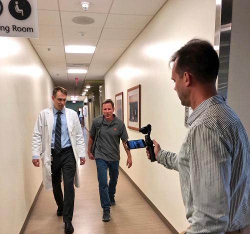 While being filmed, Tom Vibert walks the halls of Duke Cancer Center with his oncologist John Strickler, MD. The pair is to be featured in an educational video produced by the Global Colon Cancer Association. The video is expected to launch in March and will be available for viewing at globalcca.org.
