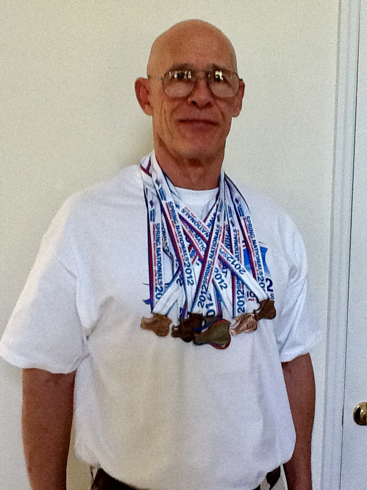 Bob List with all his masters swim meet medals.