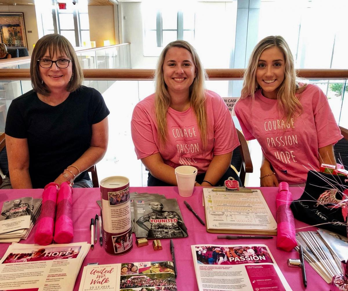 Two-time cancer survivor Mary Ann Feagan, an American Cancer Society volunteer, joins her fellow ACS volunteers Madison Blakley (center) and Nicole Larrichio (right) in signing up participants for the Duke Cancer Center Durham Making Strides team.