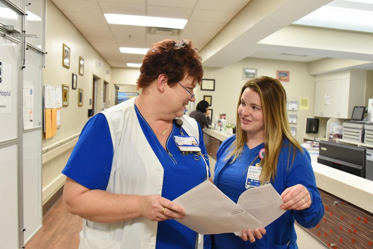 """Nicki Coates, RN, OCN, CNIII (left) and Jordan Massey, RN, BSN, CNIII (right) work together at Duke Cancer Center North Durham. """"It's like going to work with your best friend every day,""""said Massey. (photo by Karen Butler)"""