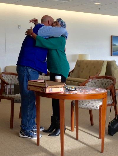 "Cancer center volunteer Jim Slaughter hugs pancreatic cancer patient Jean Spencer. They first met when they were both patients in 2014. Jim said he's grateful to his oncology team — John Strickler, MD, PA Evan Dropkin, and Sabino Zani, MD —whom he said ""pretty much pulled off a miracle."" Now he has the chance to give back."