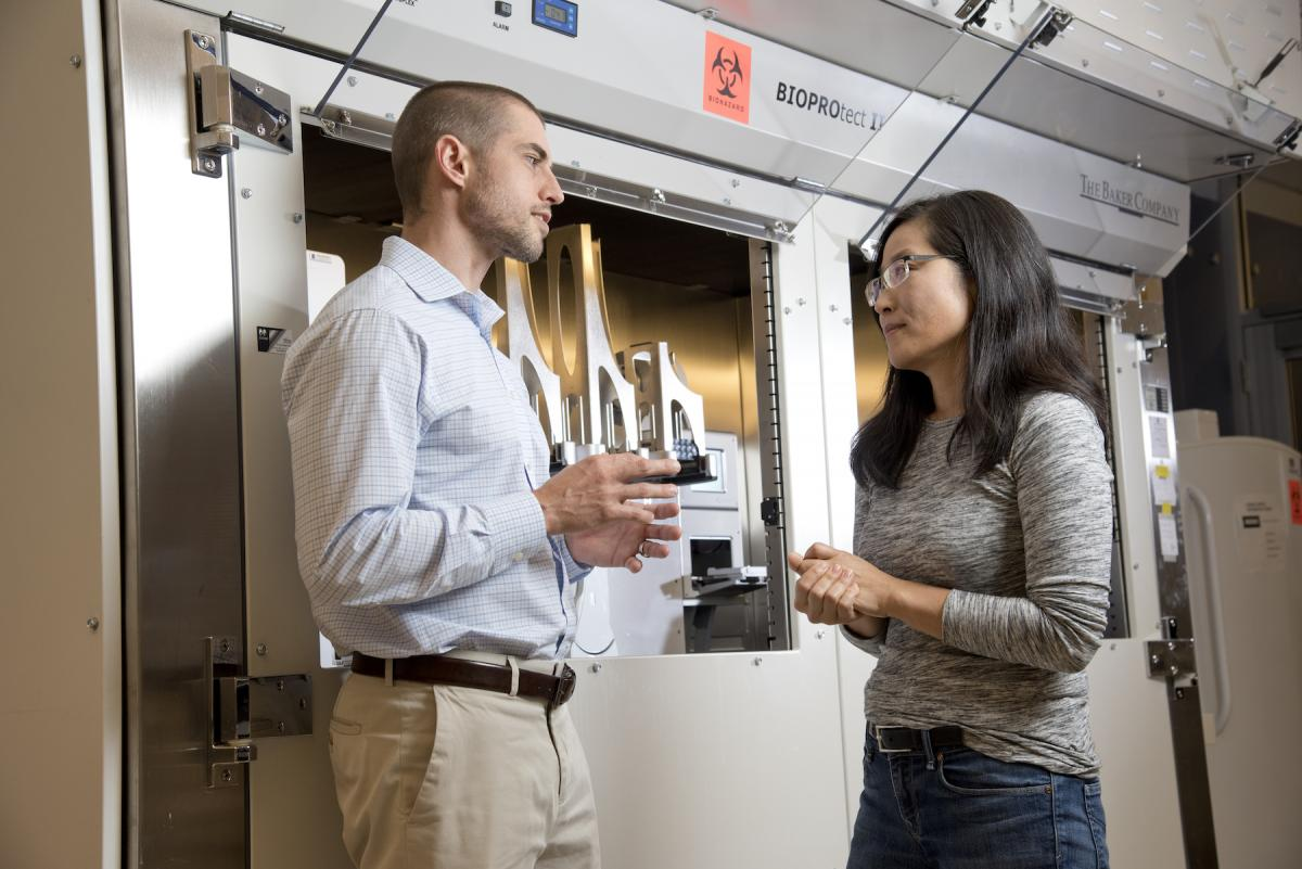 So Young Kim, PhD, updates Somarelli on the progress of testing thousands of drugs on the cell lines — both human and canine — next to the machine where it all happens. (photo by Les Todd)