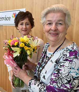 Tina Piccirilli presents flowers of appreciation to Peggy Moody, who on Aug. 2 celebrated 50 years of dedicated service at Duke.
