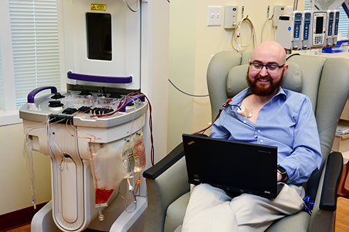 """Even while undergoing specialized treatment (photopheresis) for a bone marrow transplant complication, clinical trial coordinator Matt Williamson, RN, BSN, — with Duke's Adult Blood & Marrow Transplant Program — is hard at work at his laptop. """"To have the chance to help fight the fight against disease is such an amazing opportunity and I'm extremely grateful to be a part of that fight here at Duke,"""" he said."""