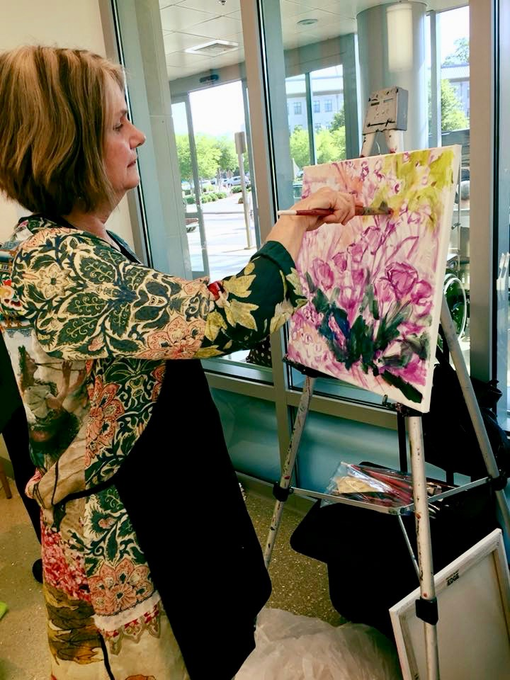 """Sally Sutton is a local artist whose """"Healing Gardens"""" paintings hang throughout Duke Cancer Center, Duke Clinics, and the hospital. Visitors to Supportive Care & Survivorship Day at Duke Cancer Center in Durham had a chance to meet the artist and watch her paint ."""