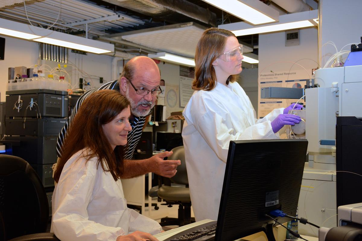 Arthur Moseley, PhD, director of the Proteomics Shared Resource, works with facility members Laura Dubois and Meredith Mayer-Salman in analyzing samples on one of the LC/MS/MS systems.