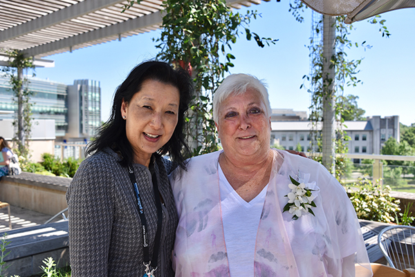 philanthropist and breast cancer survivor Donna Bernstein (right) poses for a photograph with her breast surgeon Shelley Hwang, MD, while gathered at a garden reception in her honor. Bernstein's gift established the Bernstein Family Garden, a rooftop terrace located on Level 4 of Duke Cancer Center in Durham.