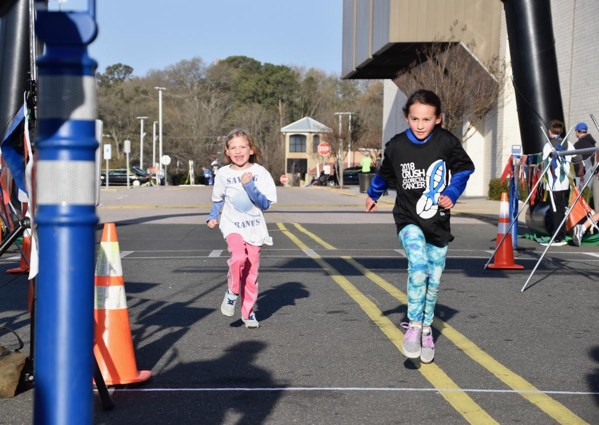 Sydney, the daughter of Duke PA Margot O'Neill, and Izzy, the daughter of colorectal cancer survivor Andy Riley, cross the finish line together at CRUSH 2018.