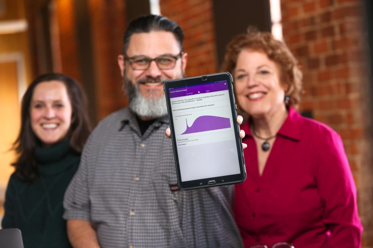 Medical student Callie Berkowitz, lead Android developer Mike Revoir, and project investigator Sophia Smith show off the Cancer Distress Coach app. (photo by Ken Huth)