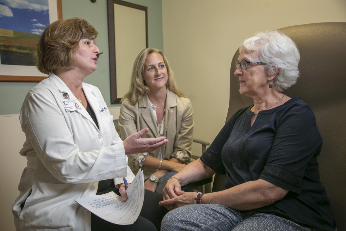 In clinic, pharmacist Lisa Vlastelica consults with pancreatic cancer patient Sandra Crossley about her prescription treatment options as her daughter, Andrea Spencer, looks on. (photo by Jared Lazarus)