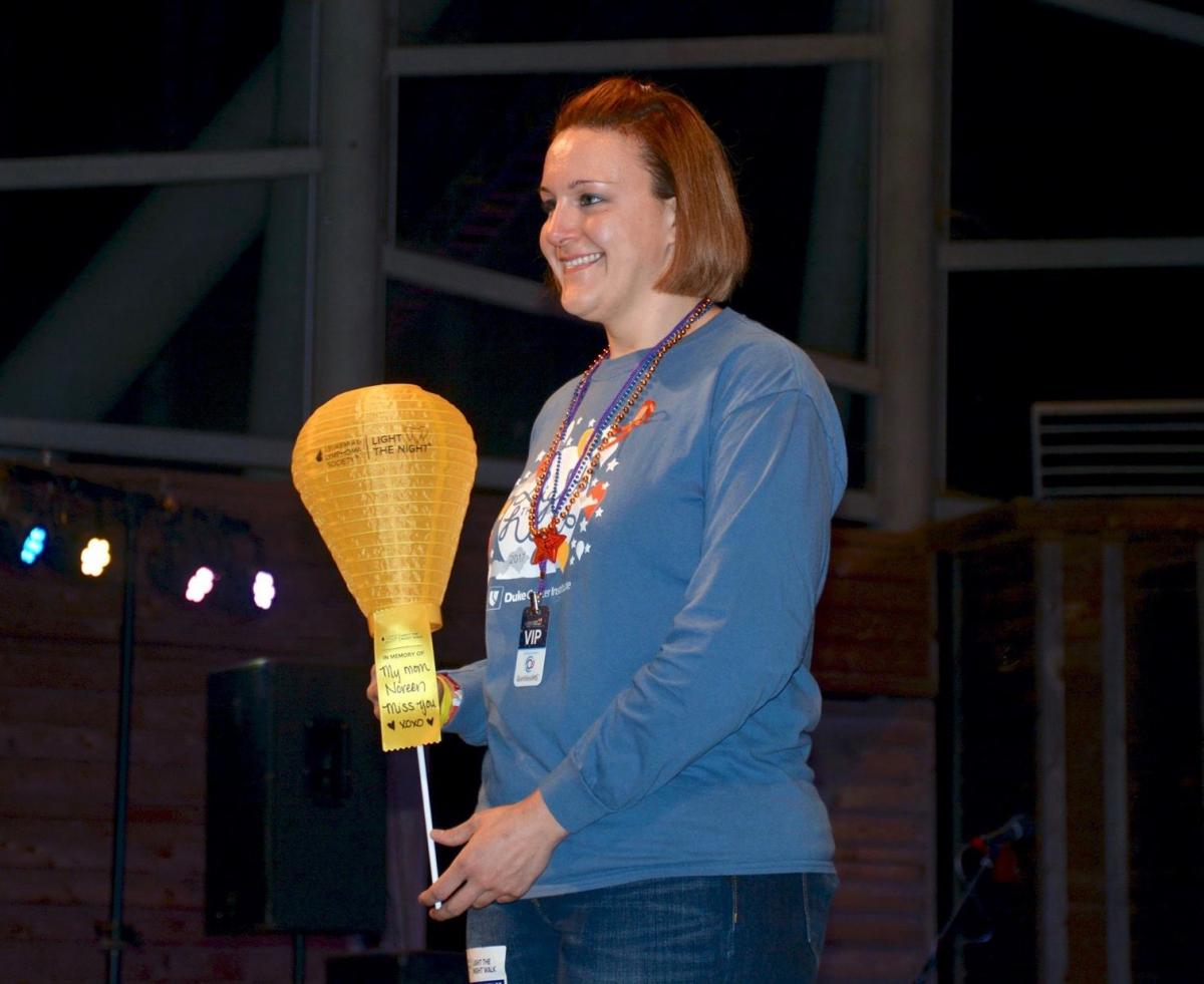 Nicole Kenney, BSN, RN, OCN, CNIII, at the 2017 Light the Night Walk, holds a gold lantern in honor of her mother Noreen's memory.