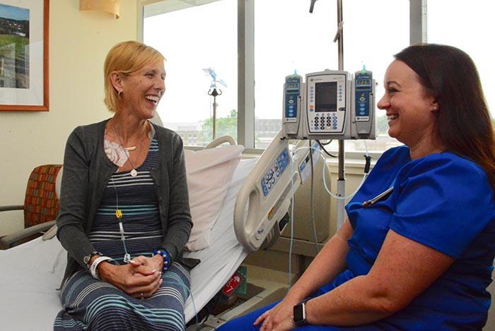 "Laura Gould-White shares a laugh with Mary Susan Moss, RN, an infusion nurse at Duke Cancer Center. Gould-White is battling stage 4 metastatic rectal cancer. After multiple lengthy hospital stays, surgeries and ongoing cancer treatments, Gould-White and her family are experiencing financial toxicity. ""The term financial toxicity is relatively new and it is used to draw parallels between the physical toxicities of chemotherapy and the cost-related burdens cancer patients feel,"" says Yousuf Zafar, MD, who has studied and written extensively on the growing problem."