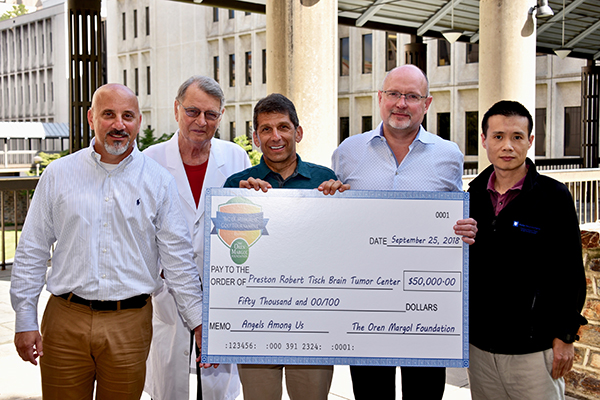 Joe Nasrallah (left) and Drew Margol (center) present a check for $50,000 to members of the Preston Robert Tisch Brain Tumor Center, including Darell D. Bigner, MD, PhD, director emeritus; Matthias Gromeier, PhD, Department of Neurosurgery; and Yiping He, Pathology.