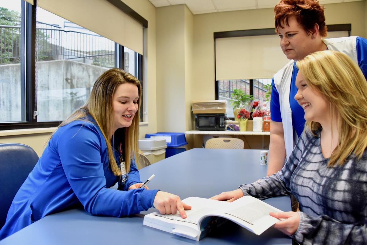 Jordan Massey, RN, BSN, CNIII (left) helped Kelly Murray, CNA (right) boost her score on a nursing school test with her hands-on teaching approach. For Jordan's mentor, Kelly's mother Nicki Coates, RN, OCN, CNIII (center), mentorship has come full circle. (photo by Karen Butler)