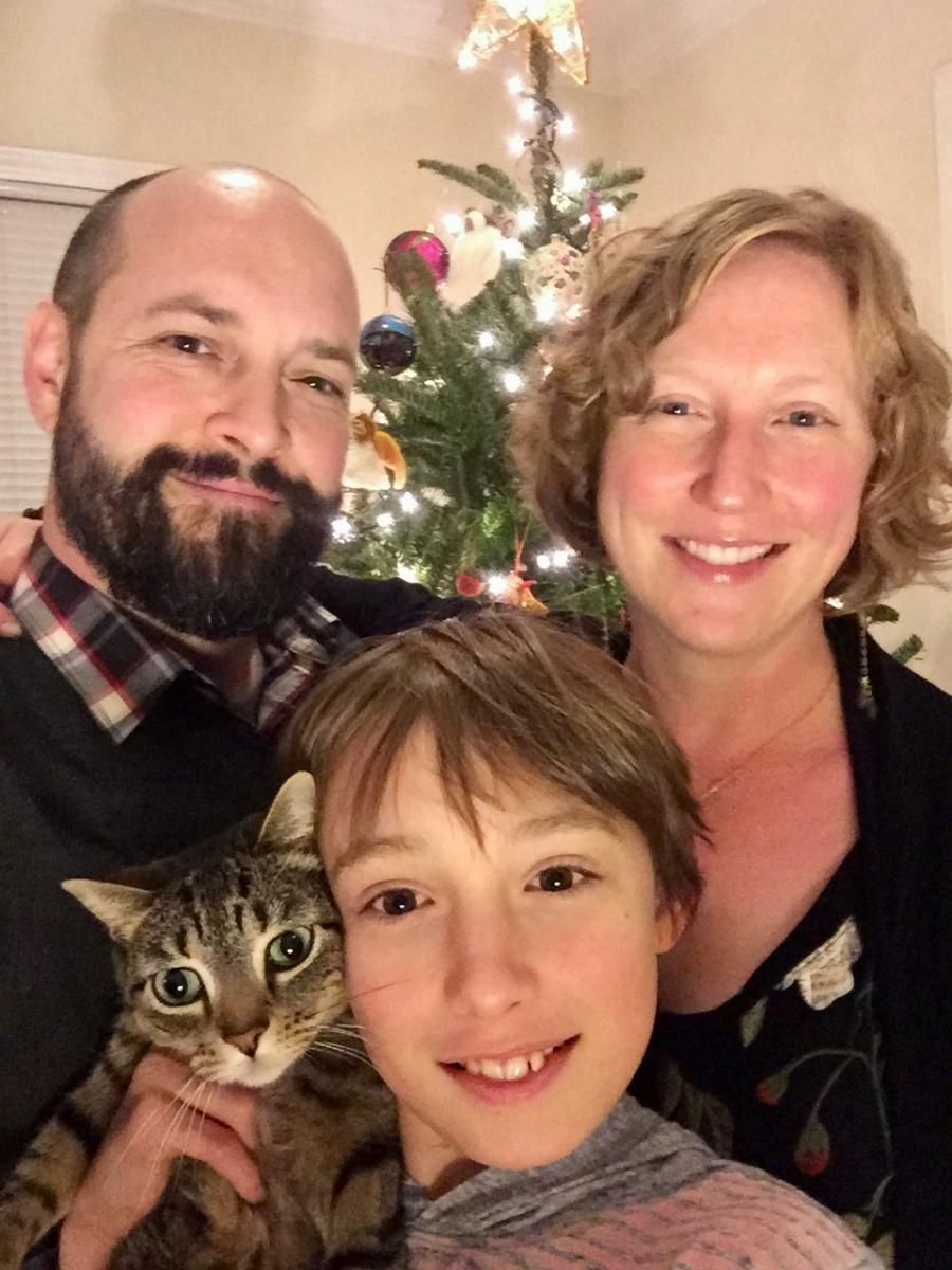 Annie, Darren and Jonas posing for a family photo, making sure to include the family cat!